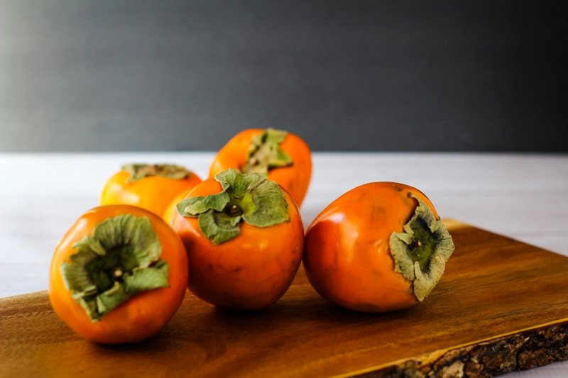 hachiya persimmons on a wooden board