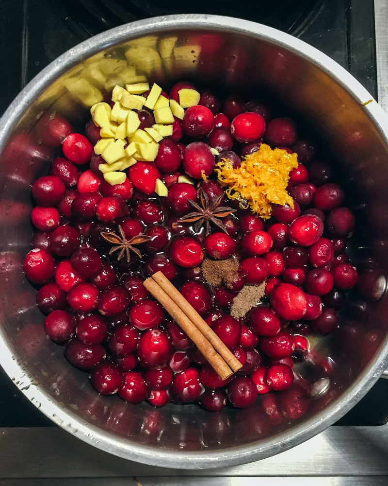 cranberries in a pot with ginger and spices