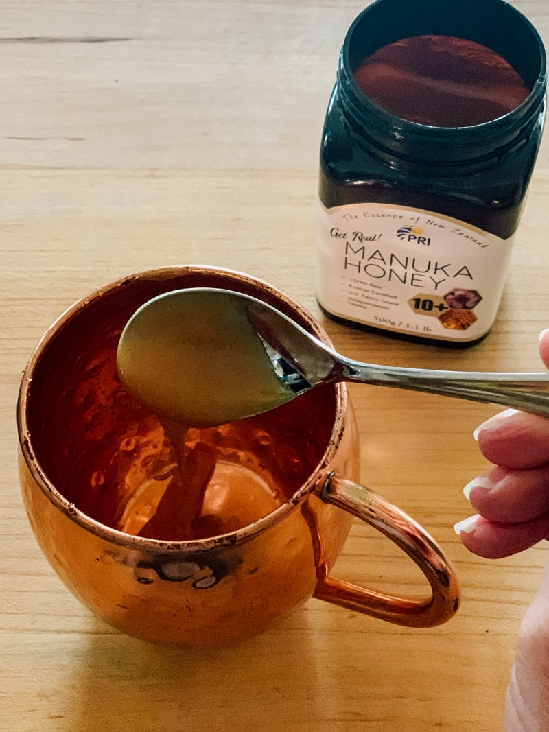 putting a spoonful of manuka honey in a mug