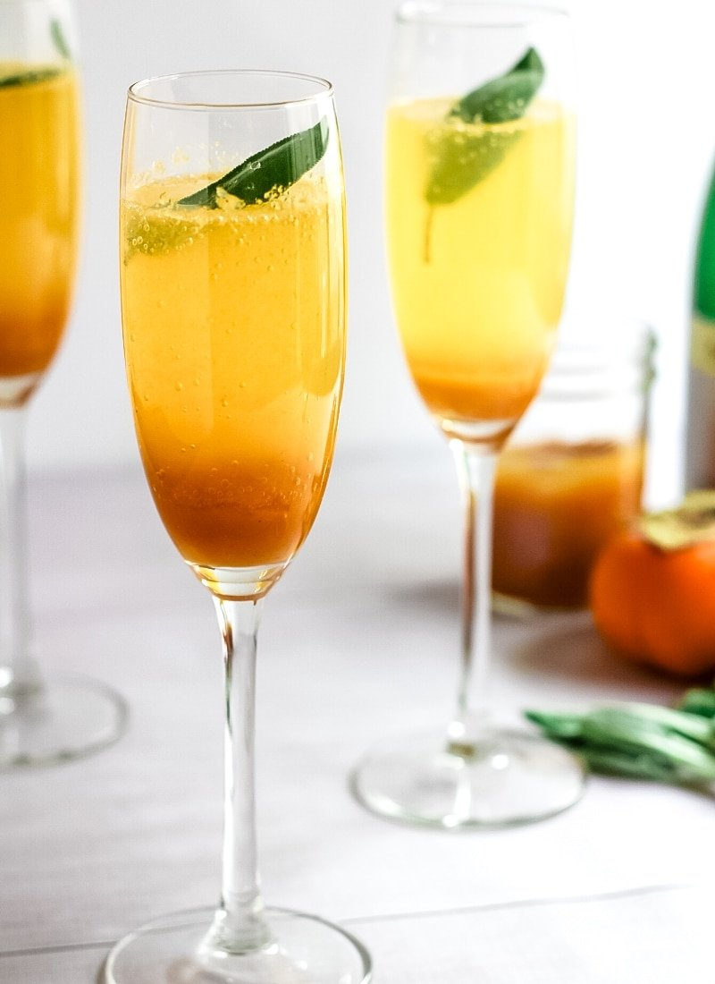 persimmon cocktail in champagne glasses