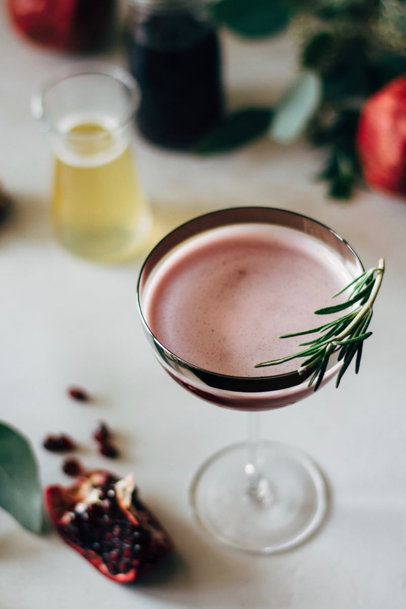 pomegranate martini with a rosemary sprig garnish