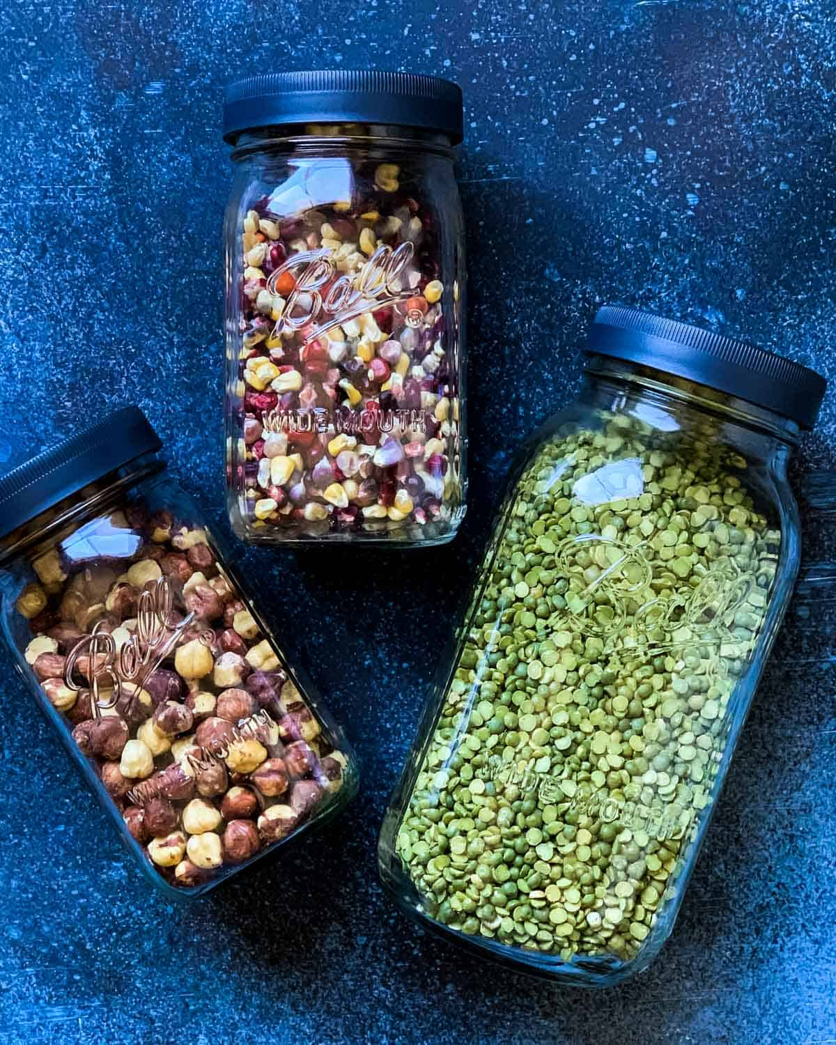 three ball jars filled with popcorn, nuts, and beans