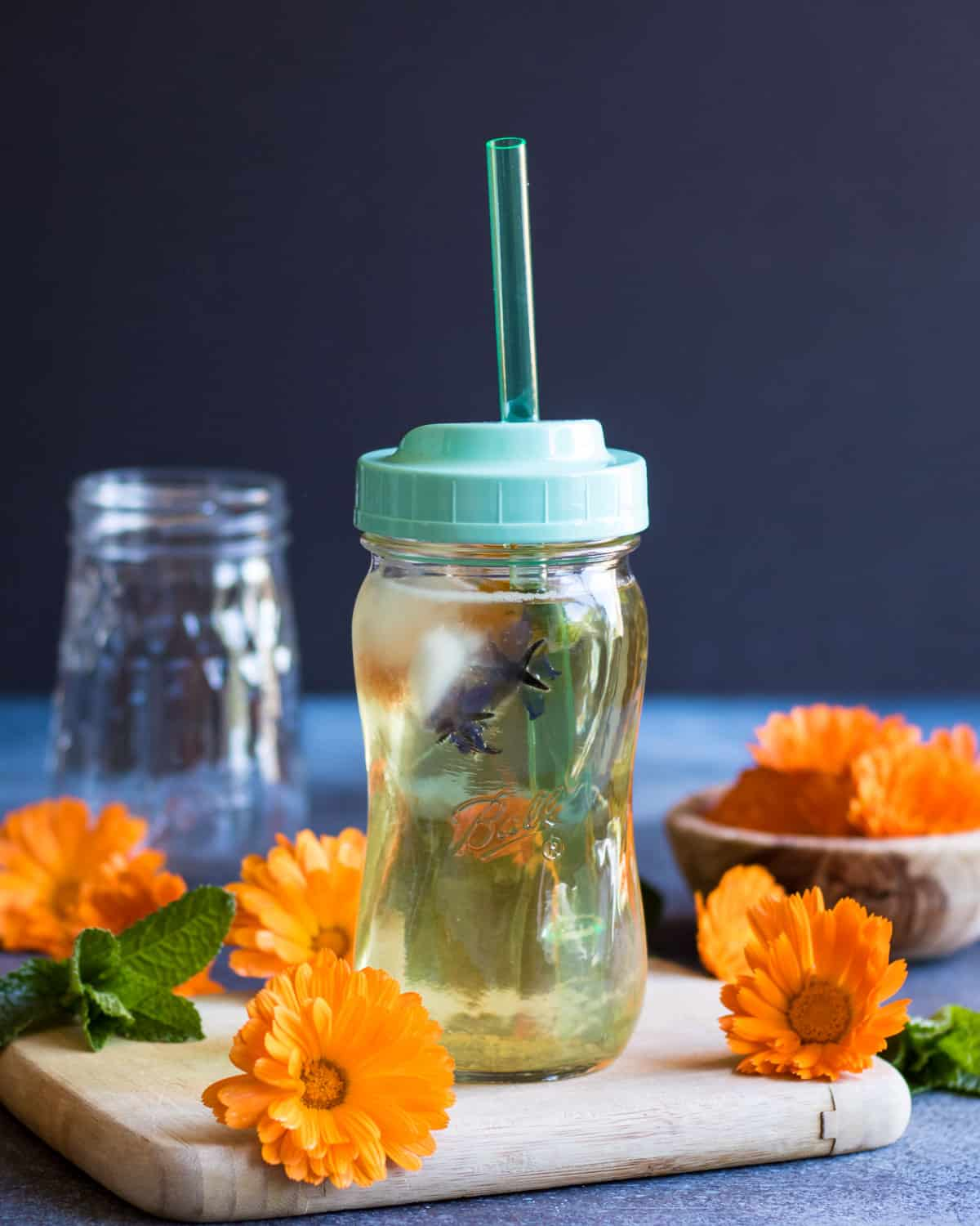 calendula iced tea served in a ball sip and straw jar