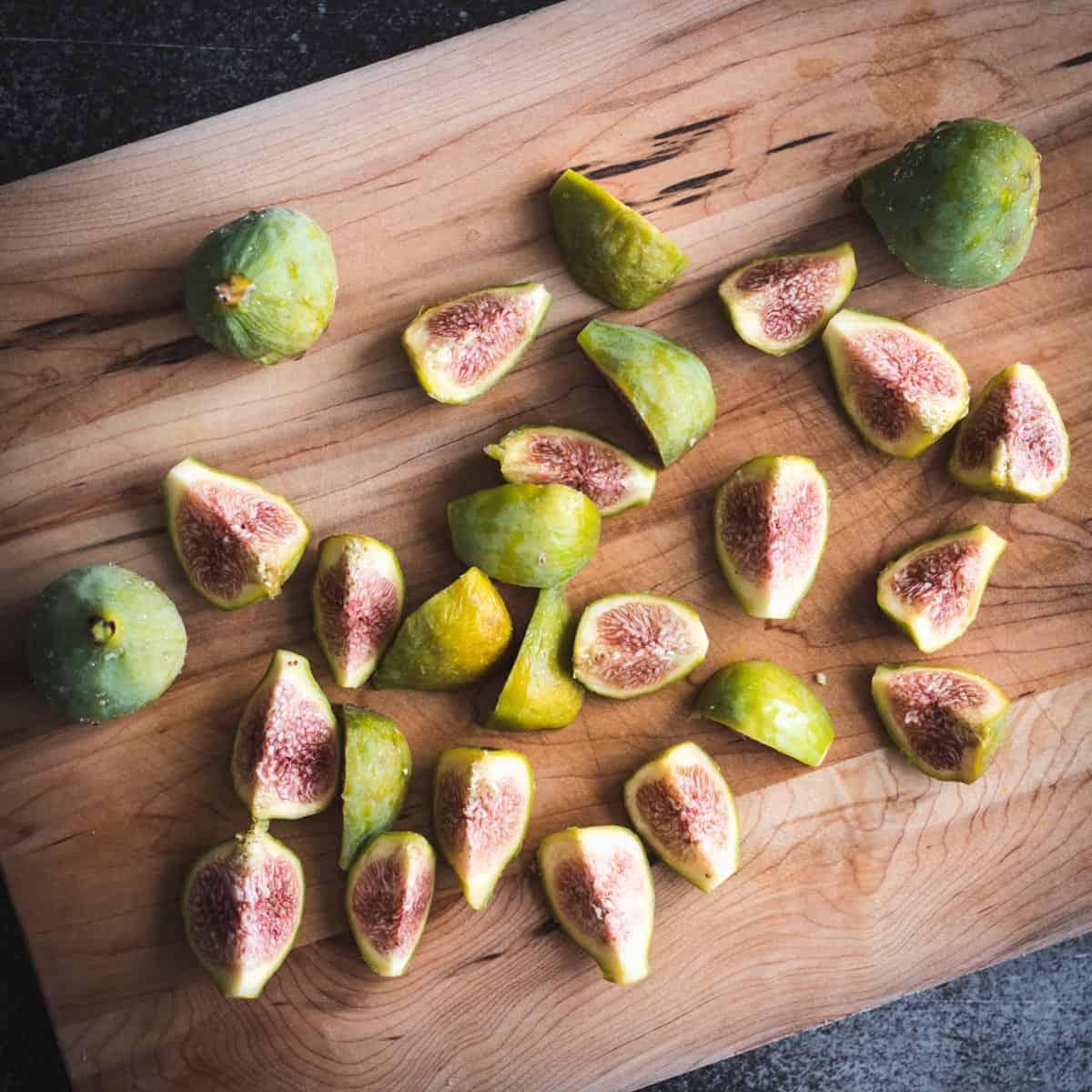 cut green figs on a cutting board