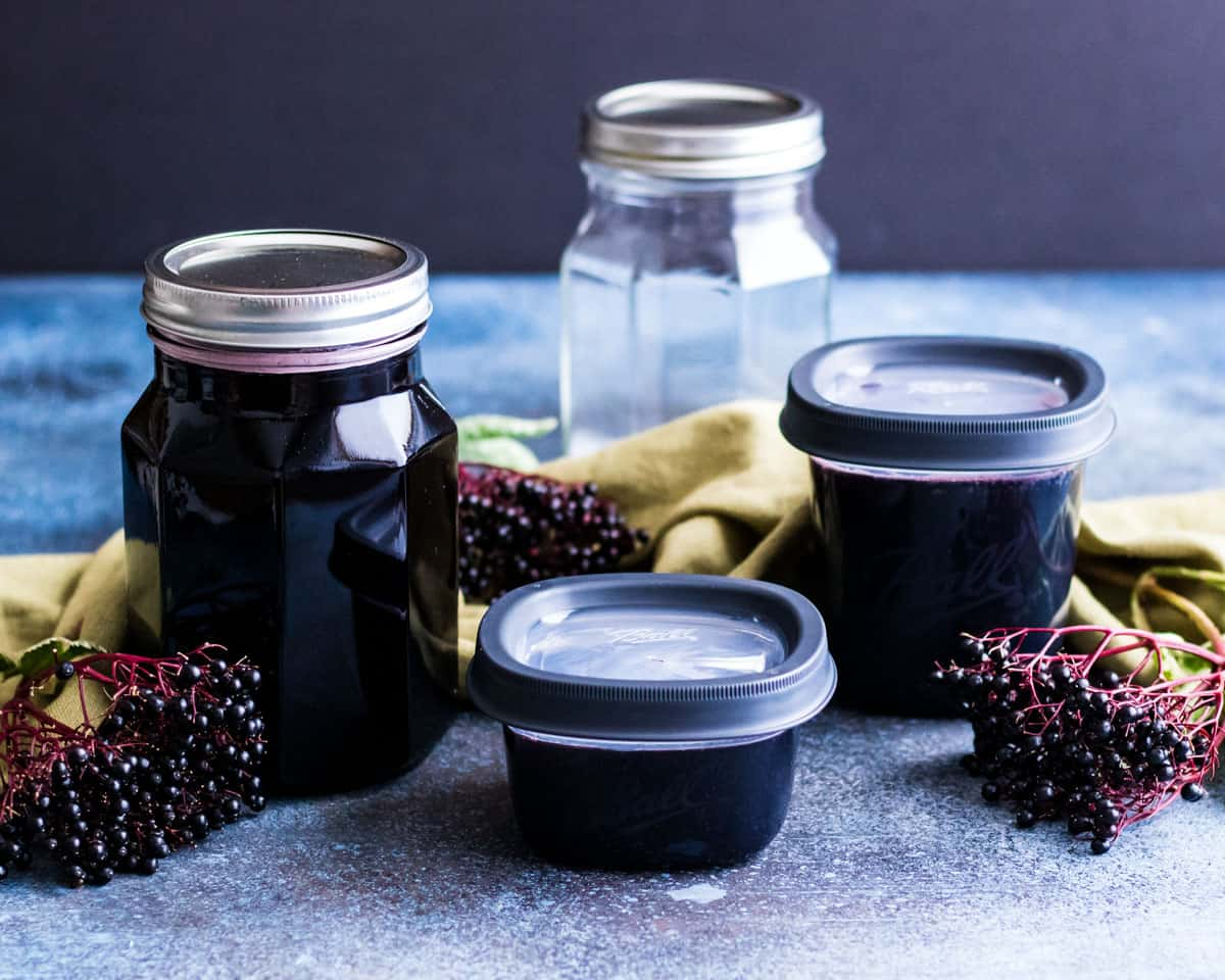 a jar and freezer jars of elderberry sryup