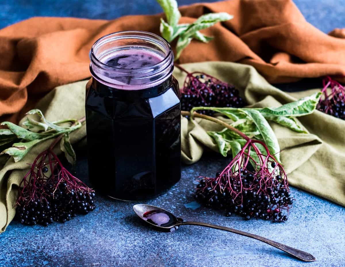 an open jar of elderberry syrup with a spoon