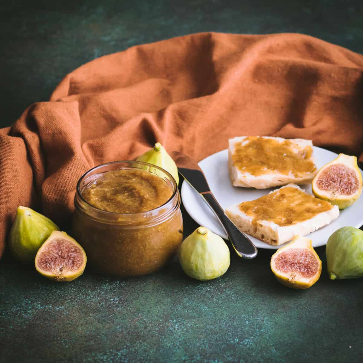 a jar of fig butter with figs on a table