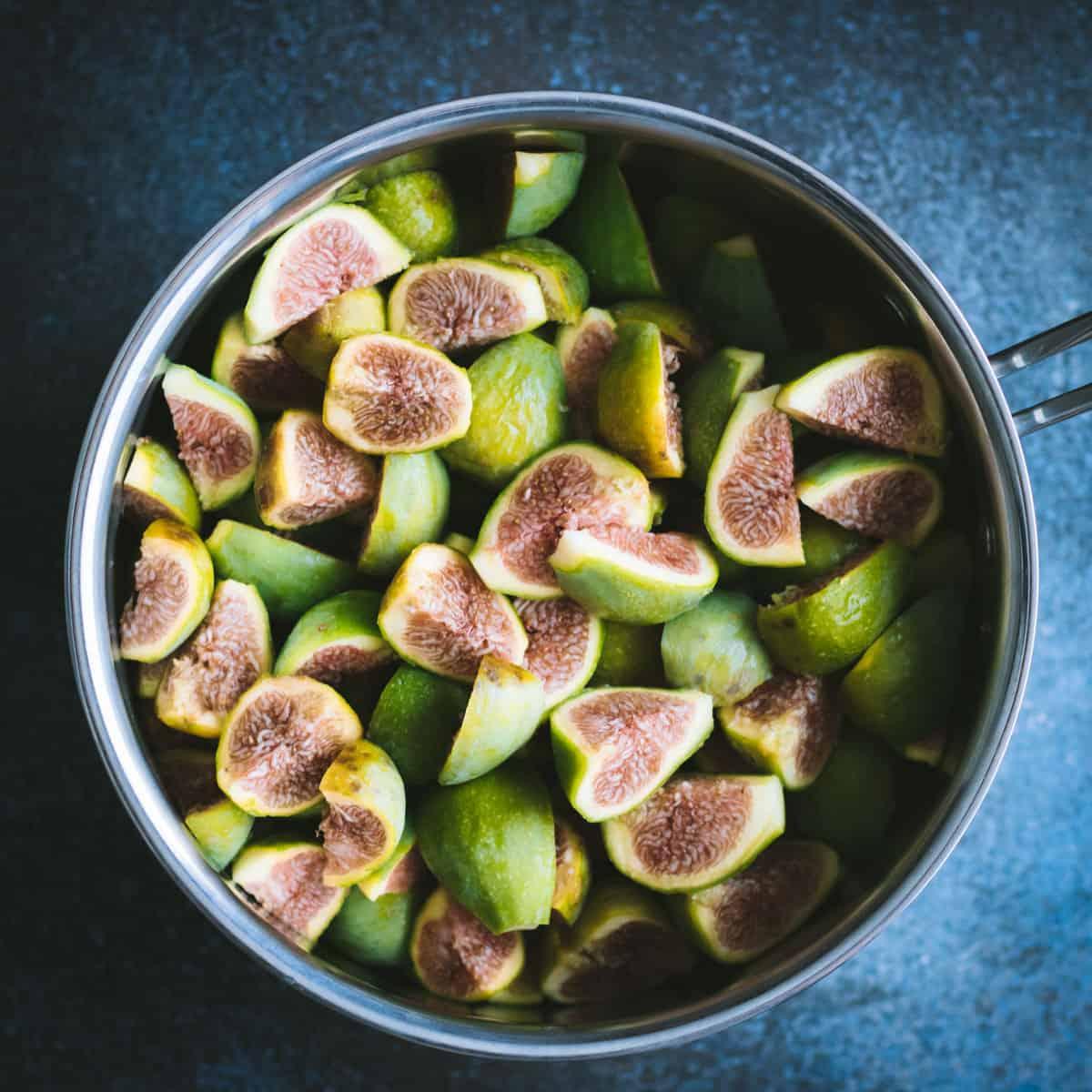 cut green figs in a pot