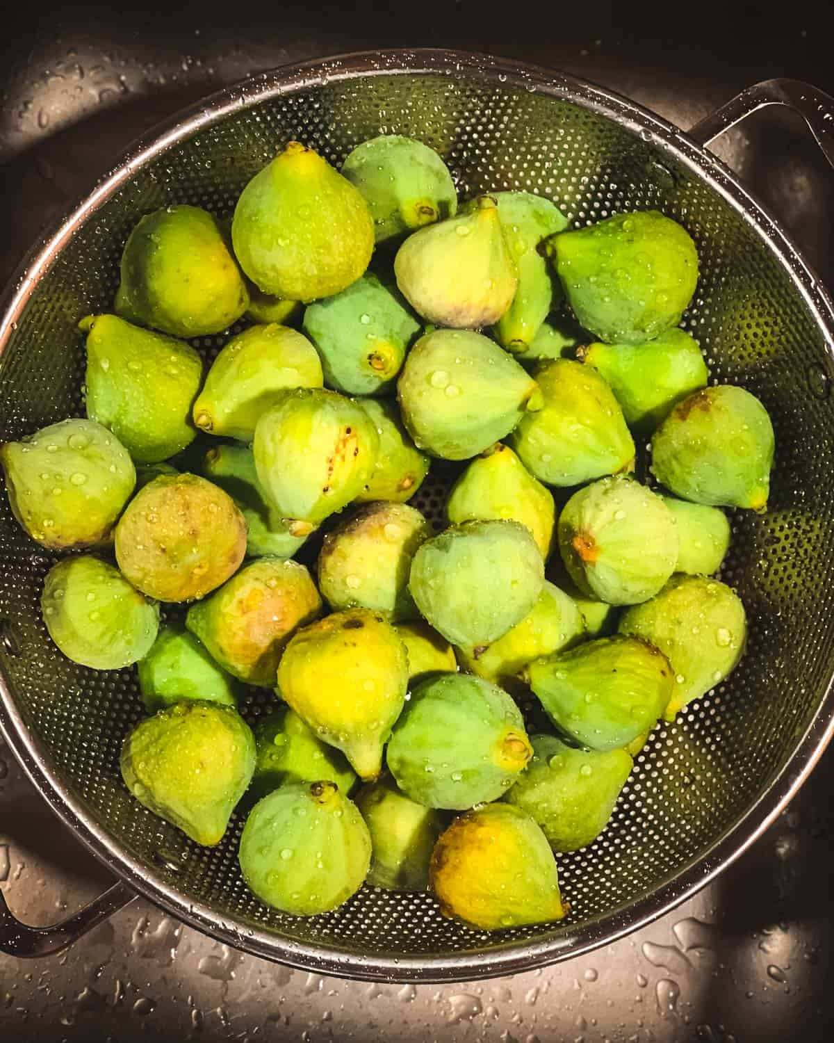 green figs being washed in a sink