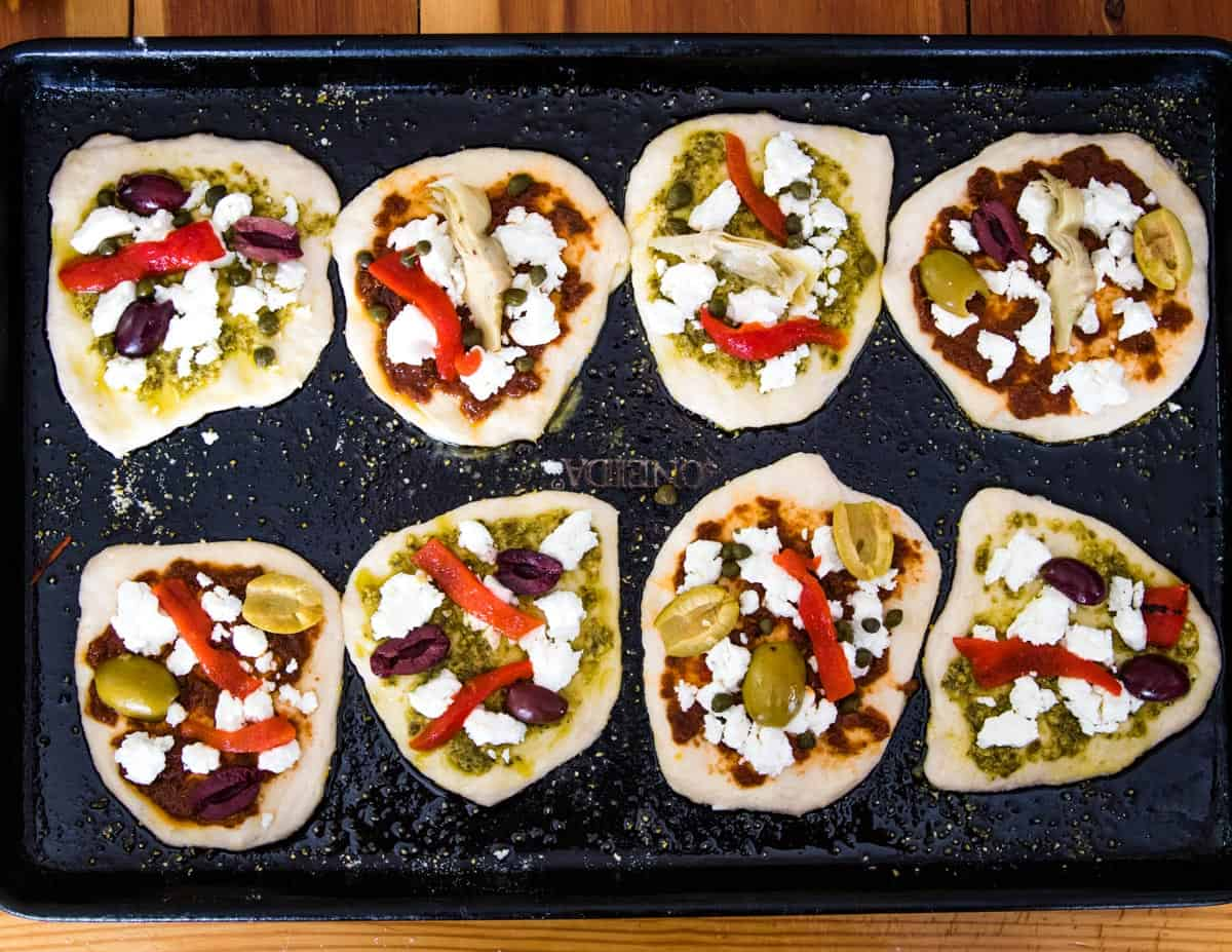 mini sourdough pizzas on a sheet pan waiting to be baked