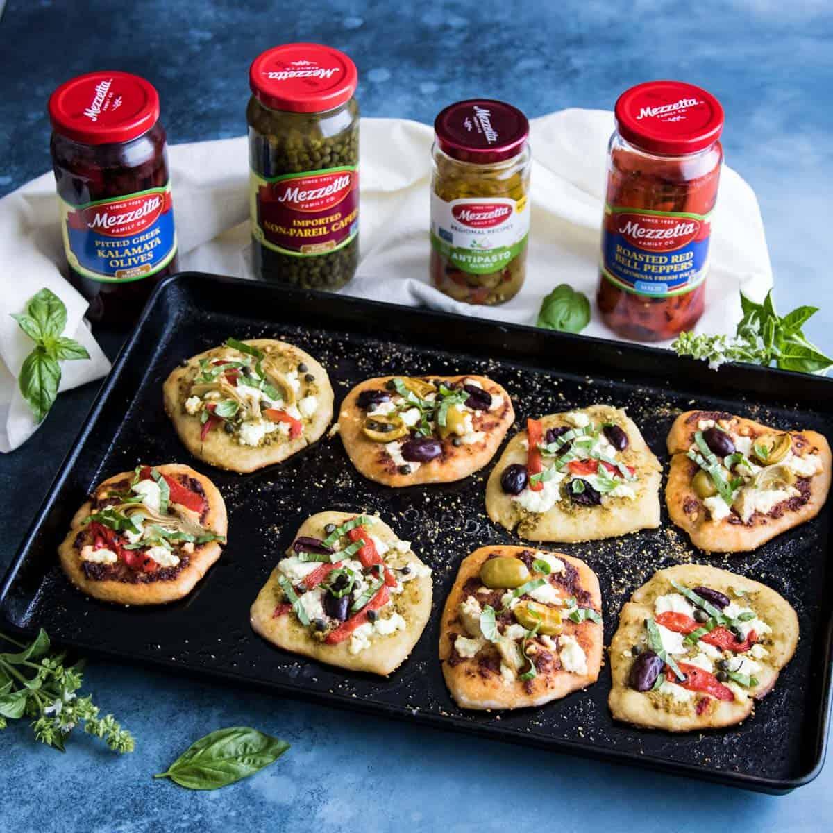 mini sourdough pizzas on a sheet pan with jars of Mezzetta ingredients