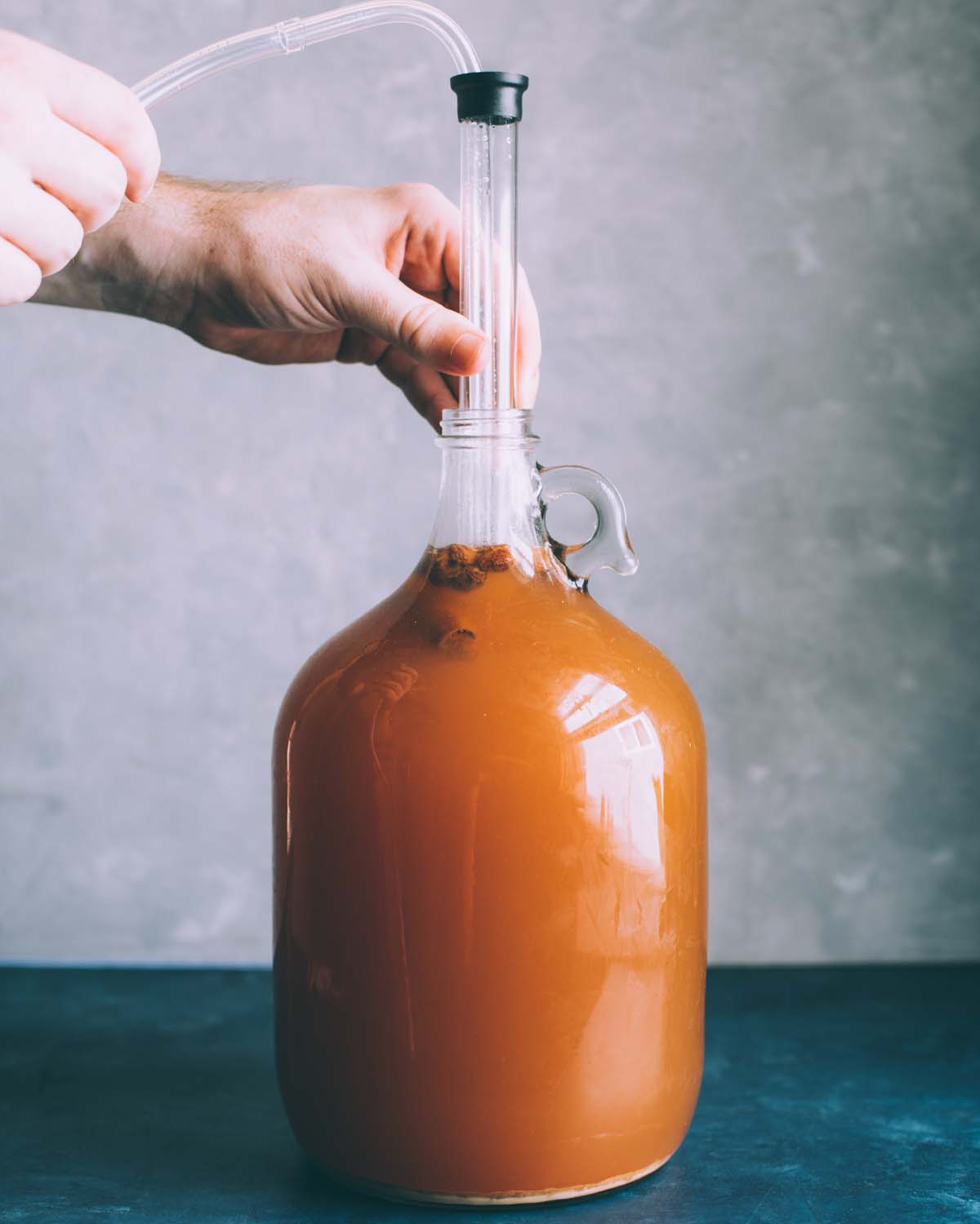 a hand putting the auto siphon into the jug of cider