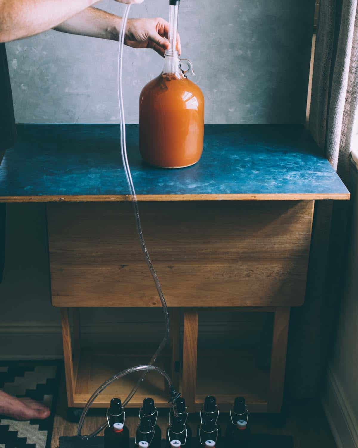 a hand holding the auto siphon in a jug of cider with tubing going down to the bottles on the floor