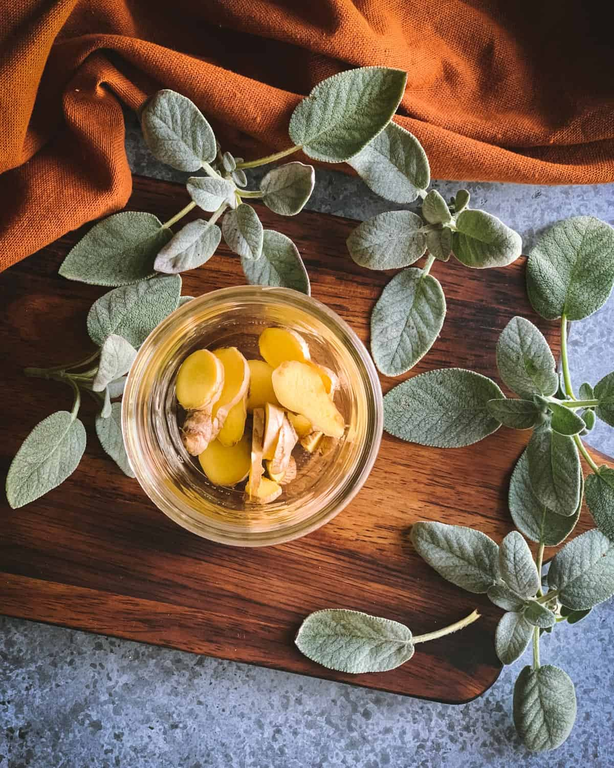 sliced ginger pieces in a pint jar with sage on the table