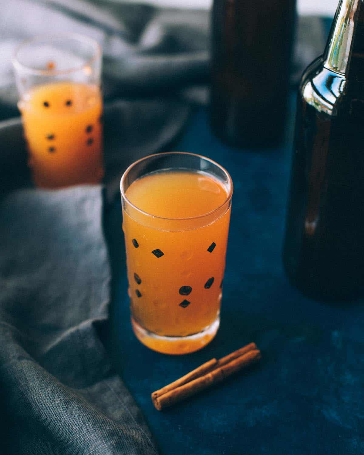 a glass of hard cider on a table with a cinnamon stick