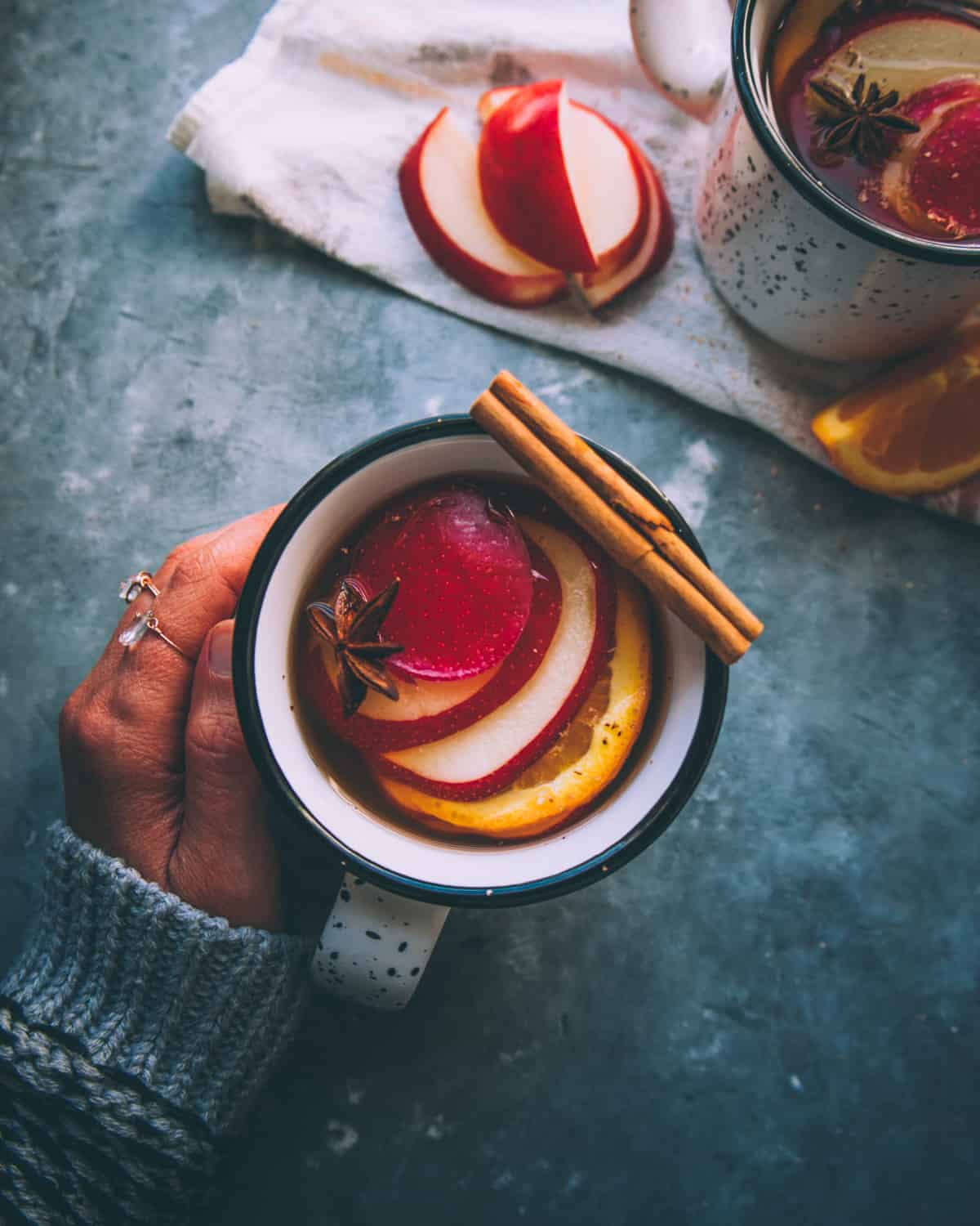 a mug of mulled hard cider on a table with a hand around it