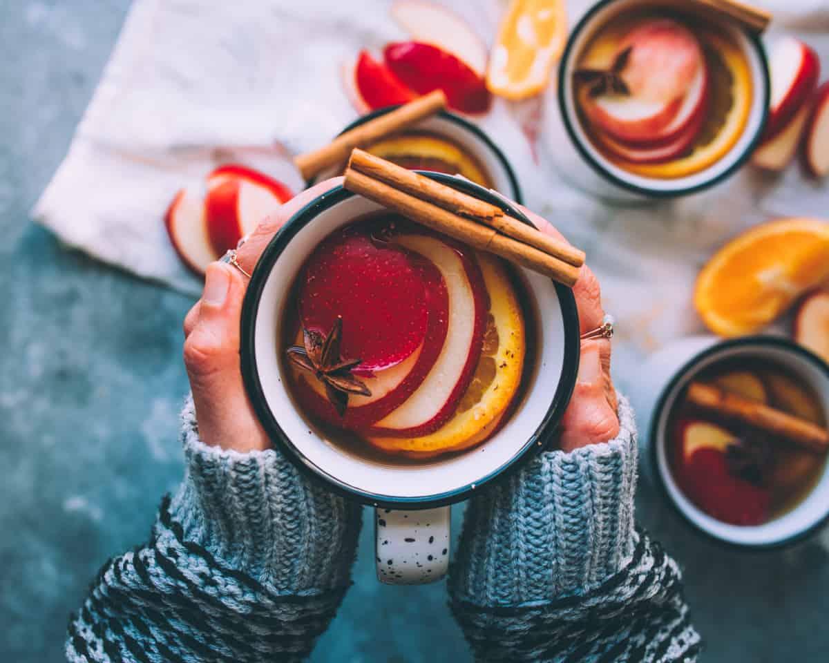 two hands holding a mug of mulled hard cider