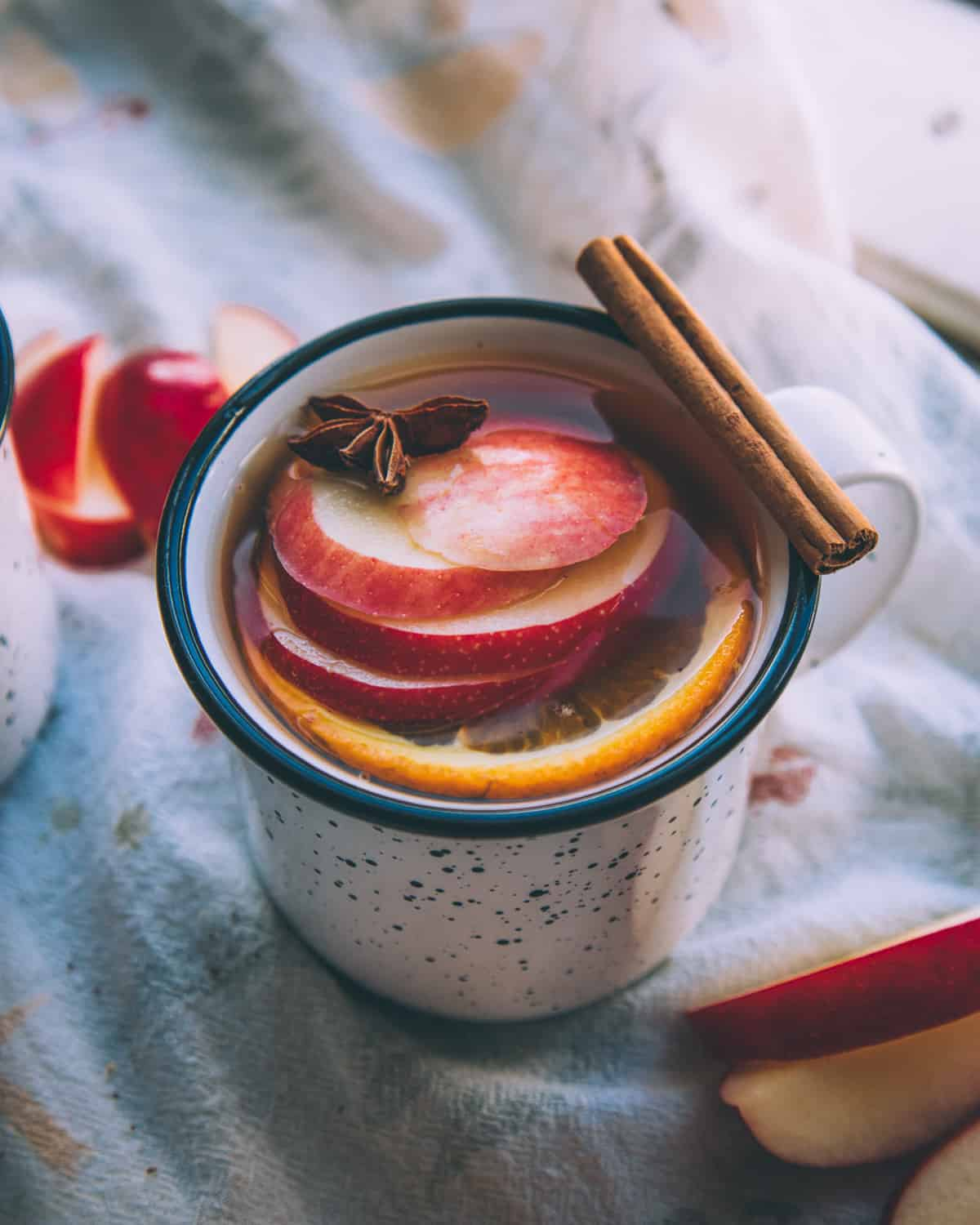 a mug of mulled hard cider with apples and a cinnamon stick for garnish