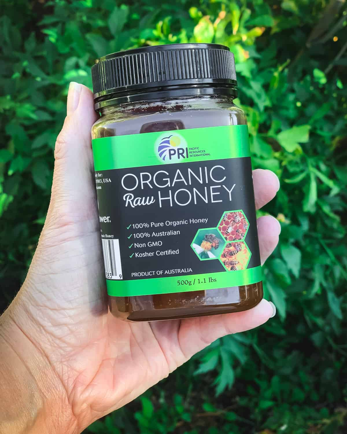 a hand holding a container of organic raw honey from pri