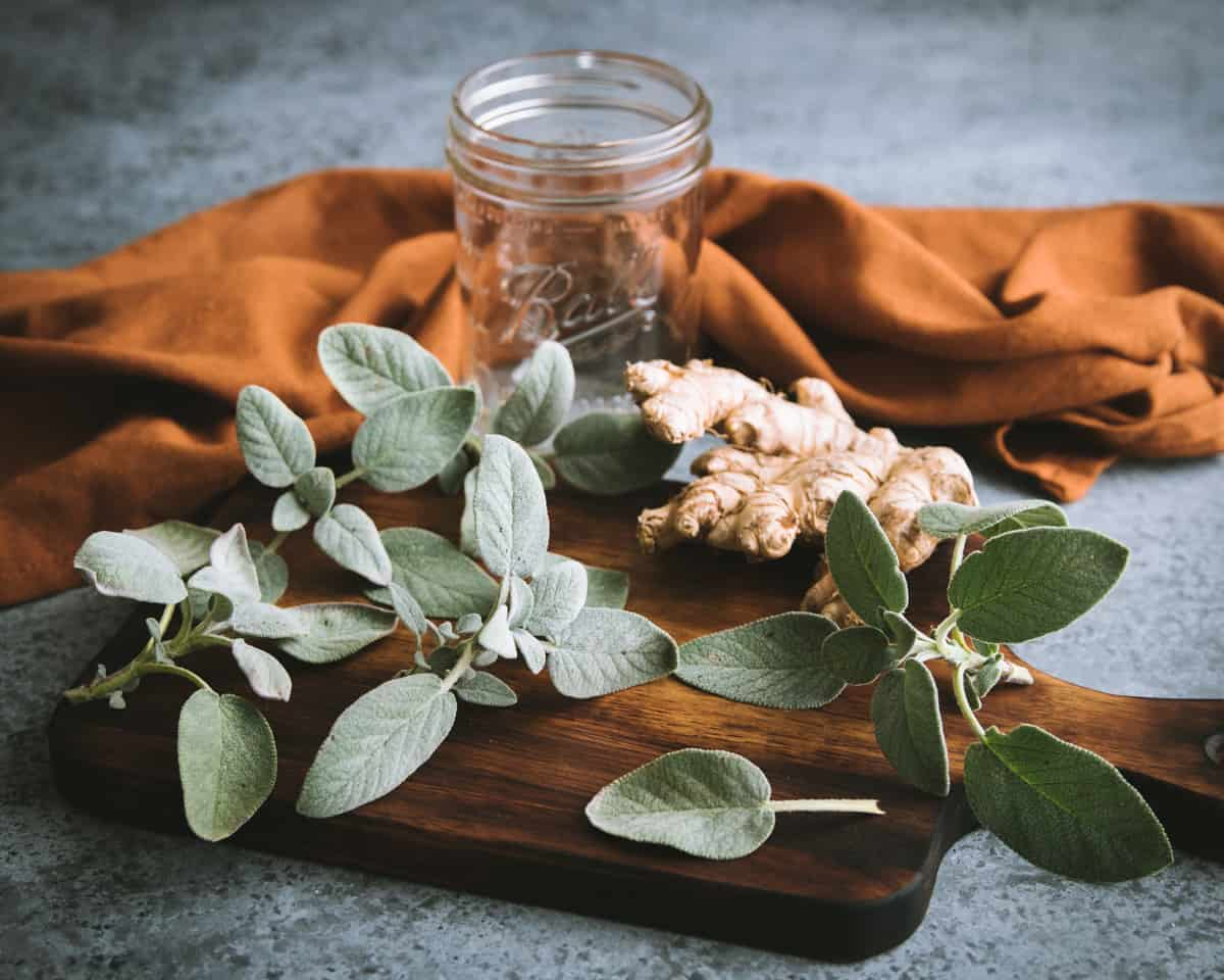 fresh sage and ginger on a cutting board with a ball jar