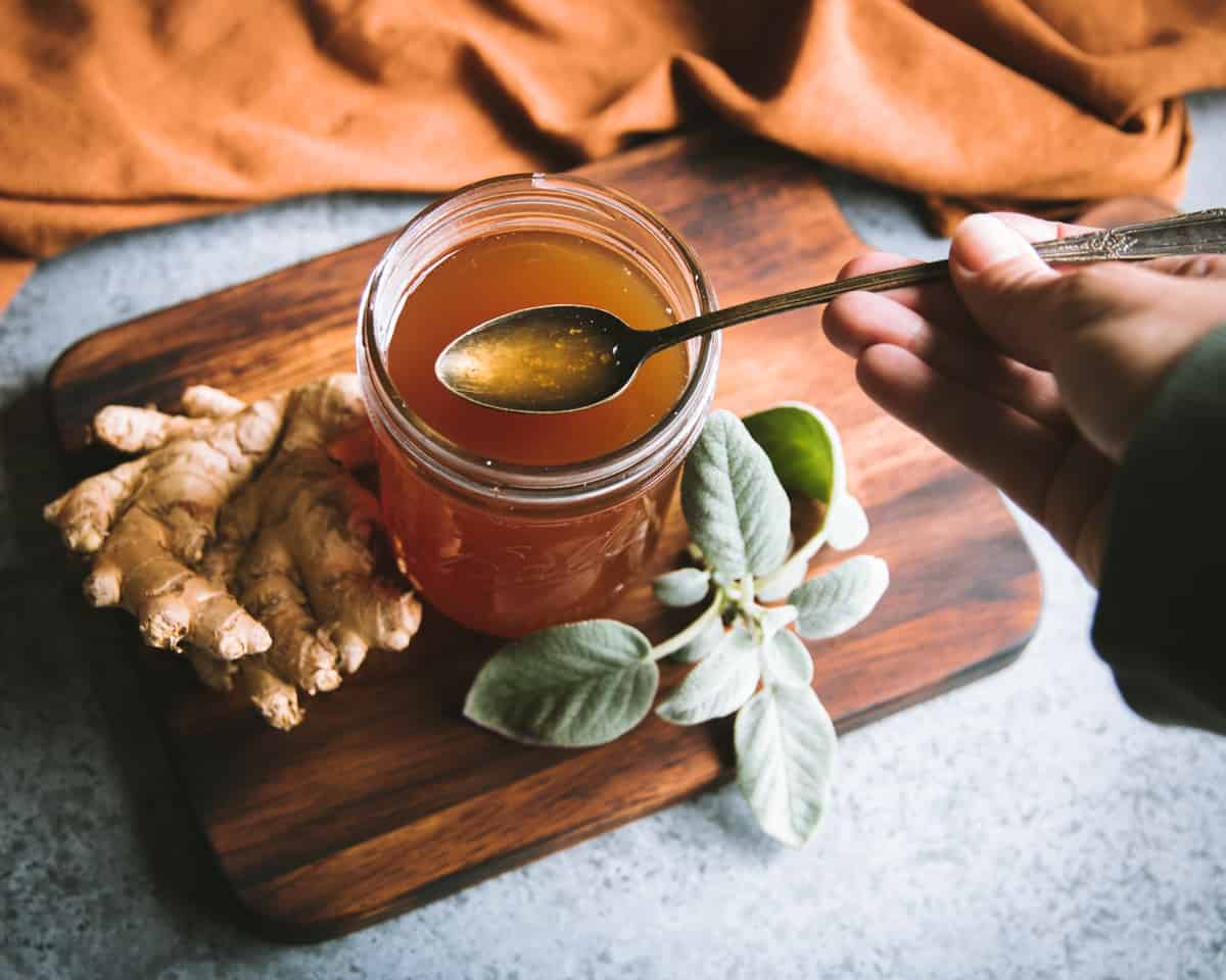 a hand holding a spoonful of sage and ginger oxymel