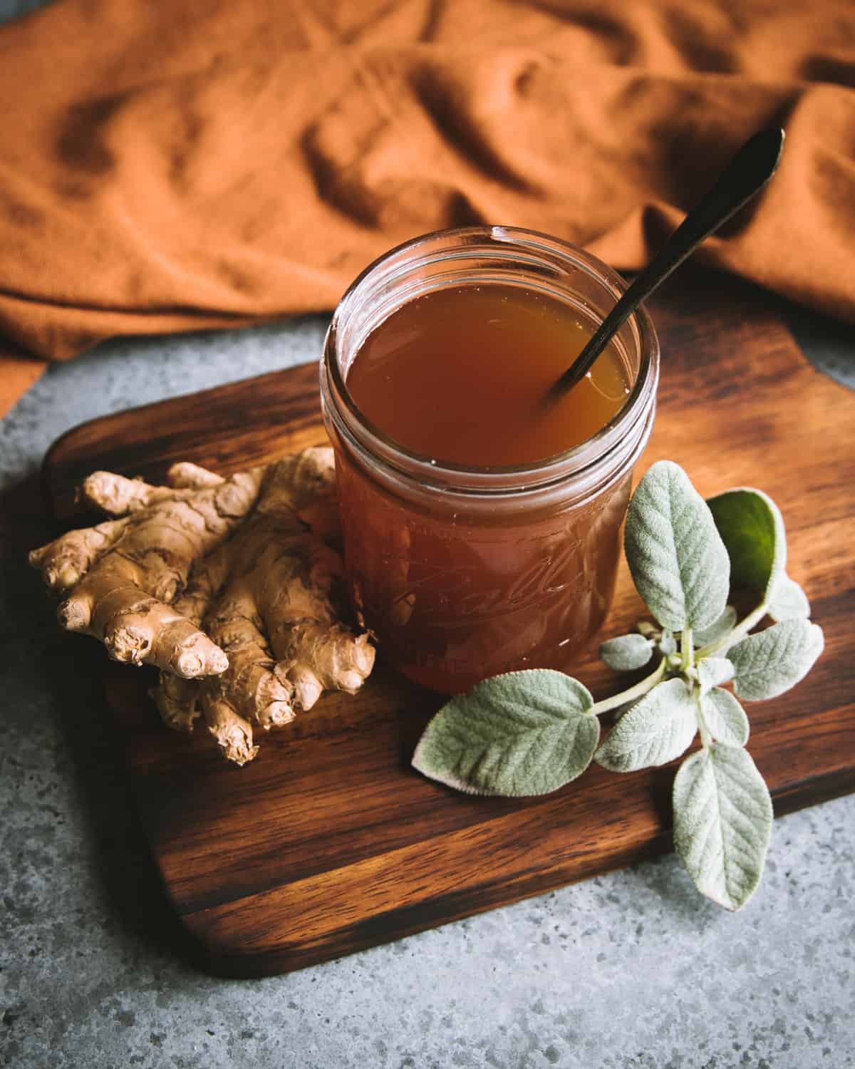 a jar of sage and ginger herbal oxymel with a spoon
