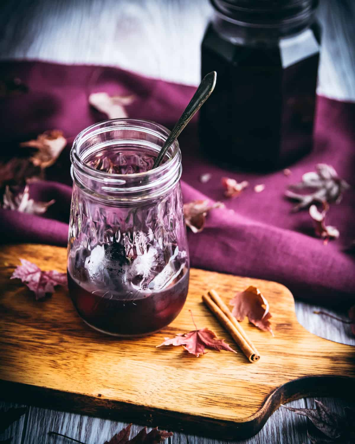 elderberry syrup in a jar with ice and a spoon