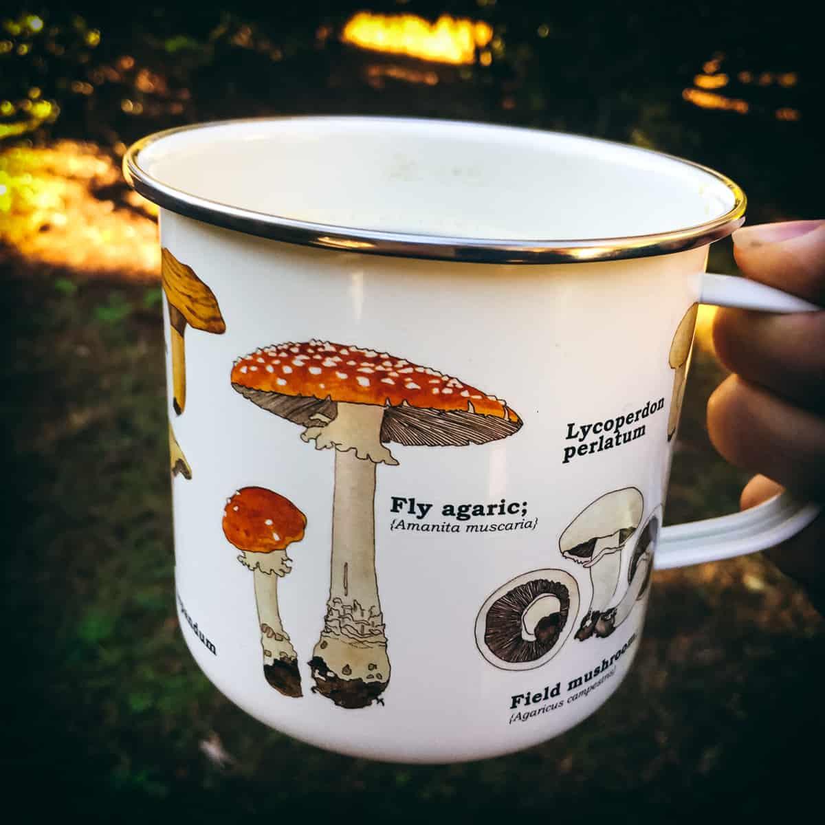 a hand holding a mushroom mug