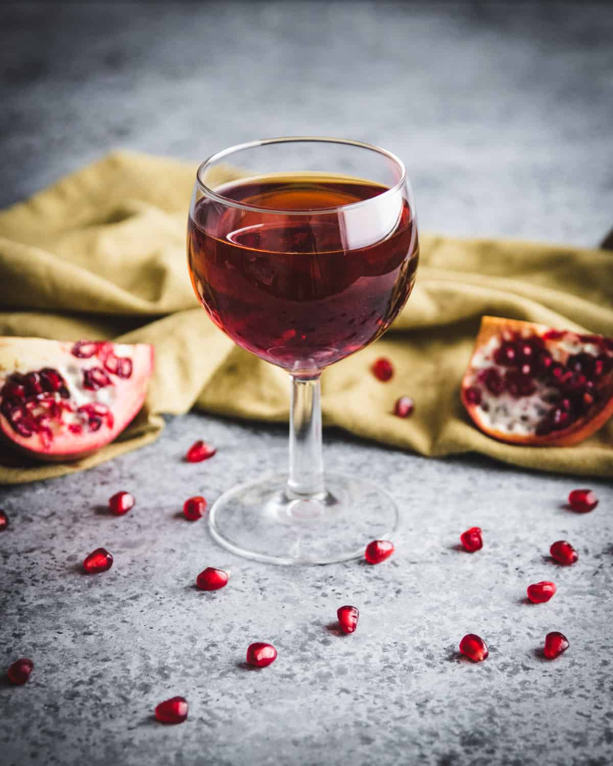 a glass of pomegranate wine on a table with pomegrante seeds
