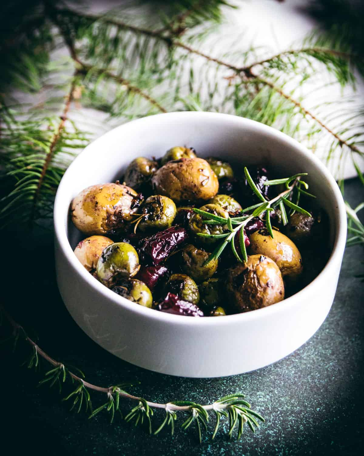a bowl of roasted olives with rosemary