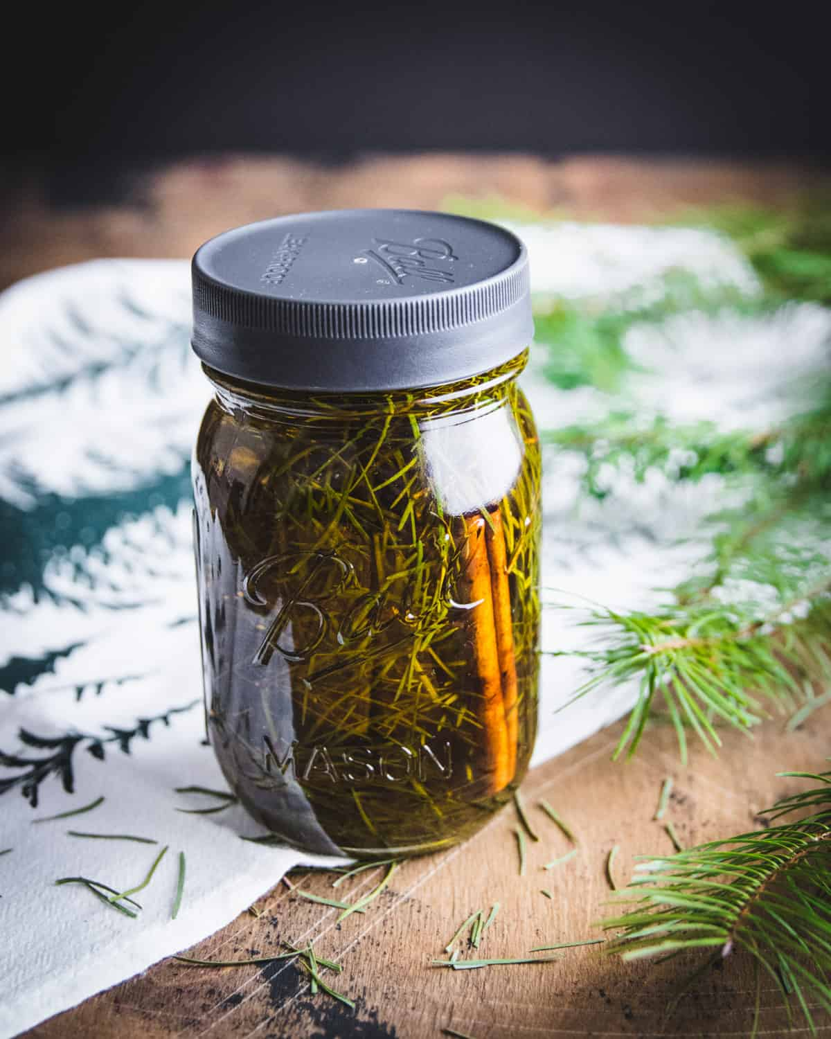 a jar of conifer infused oil with a cinnamon stick