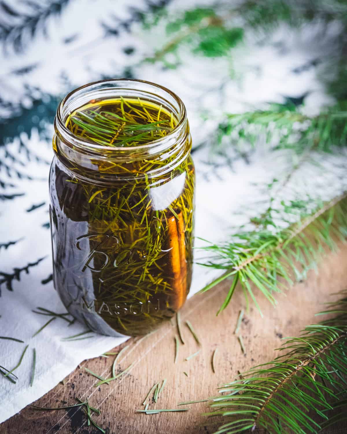 an open jar of conifer needles infusing in oil