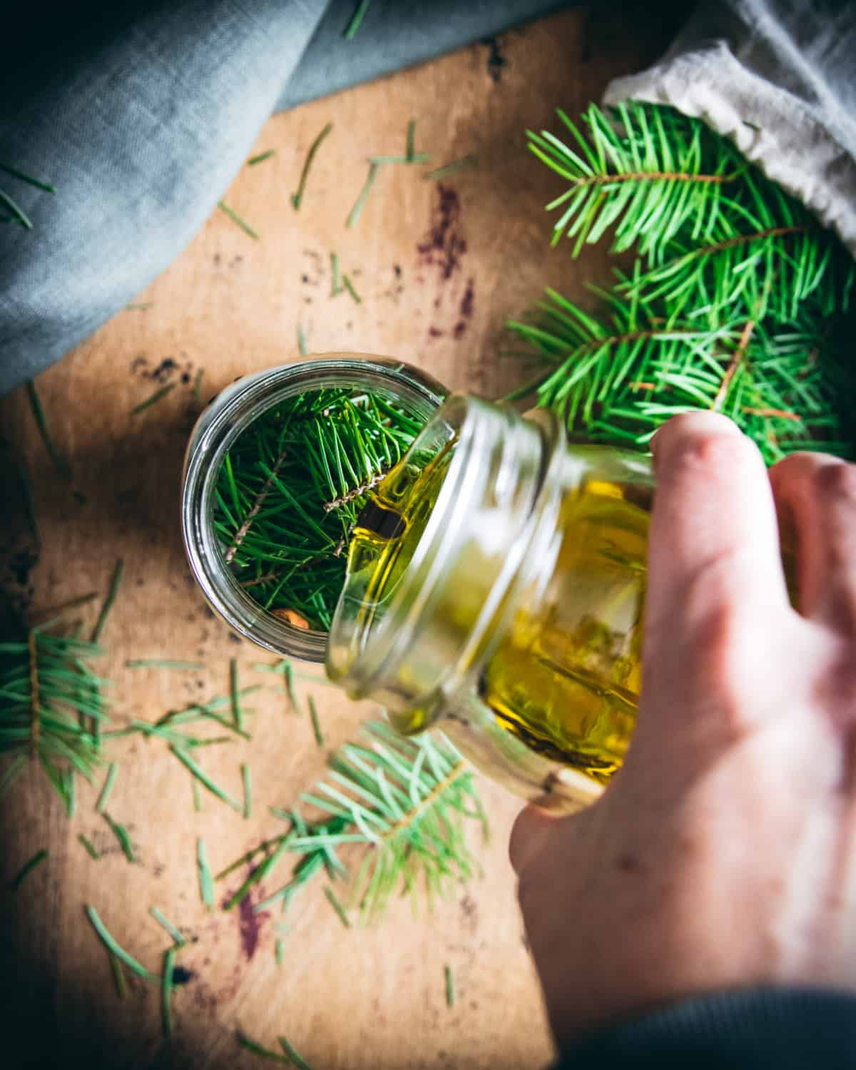 a hand pouring olive oil into a jar of conifer needles