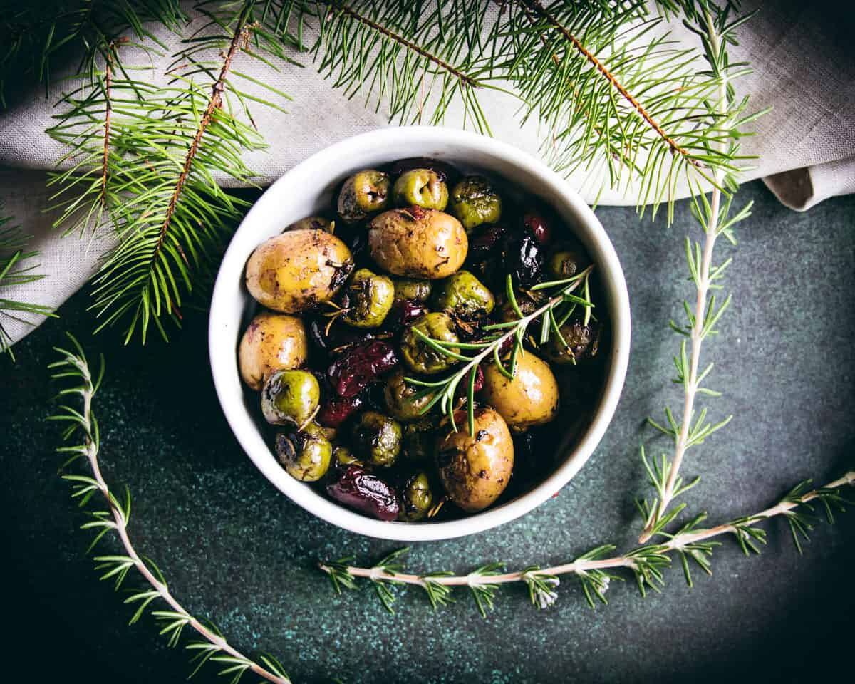a bowl of roasted olives with rosemary garnish