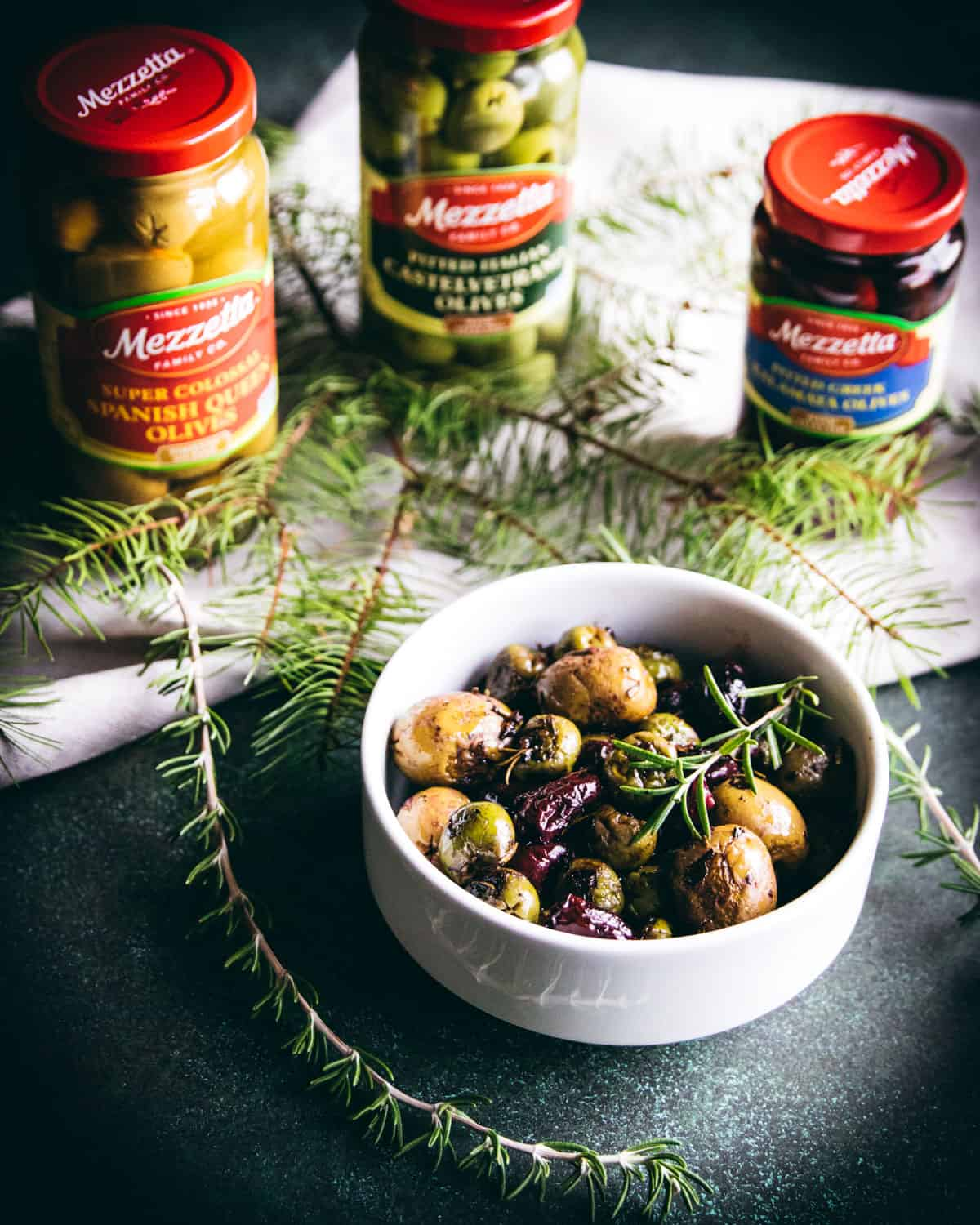 a bowl of roasted olives on a table with some jars of Mezzetta olives