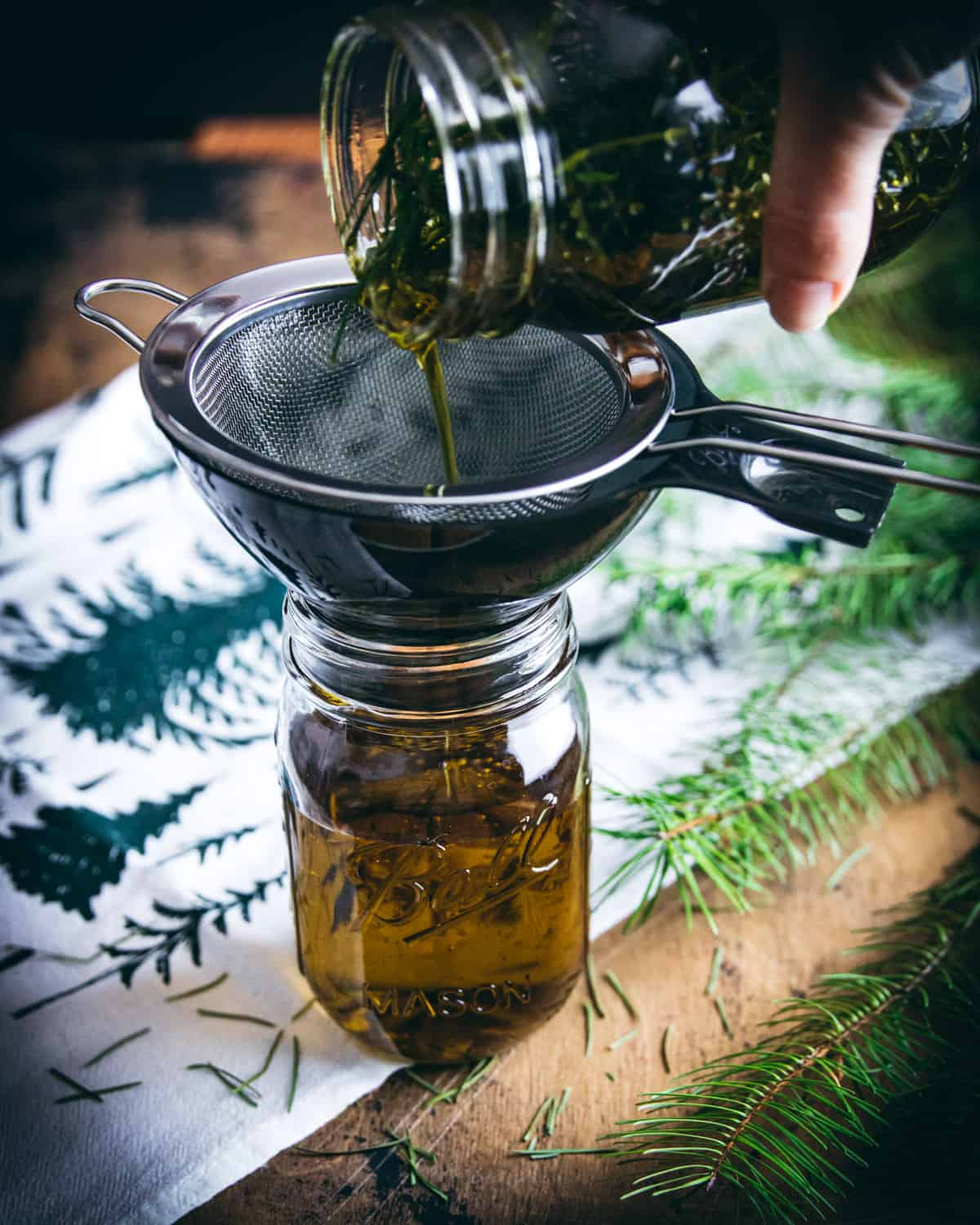 pouring the conifer infused oil through a strainer