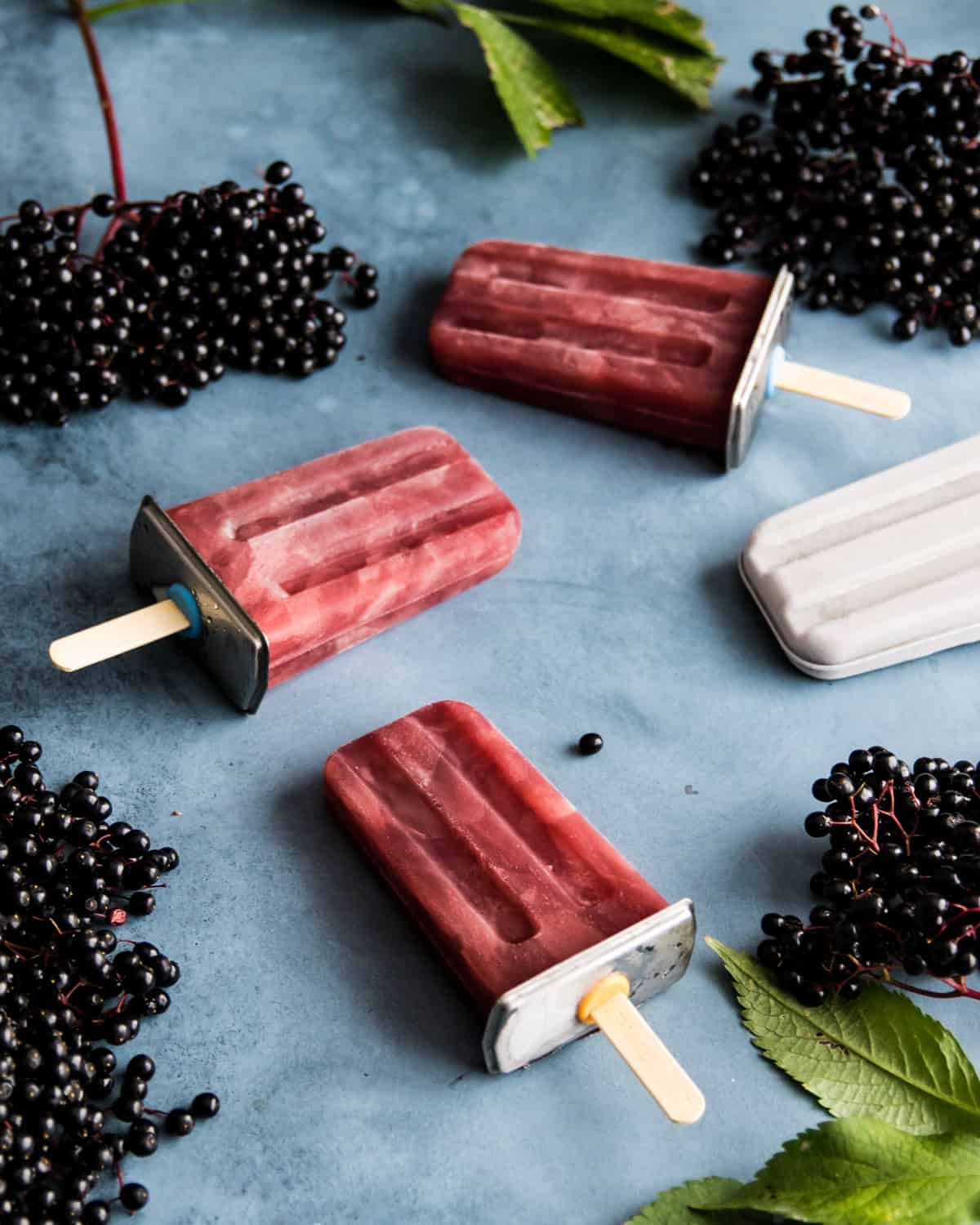 three elderberry popsicles on a table with fresh elderberries