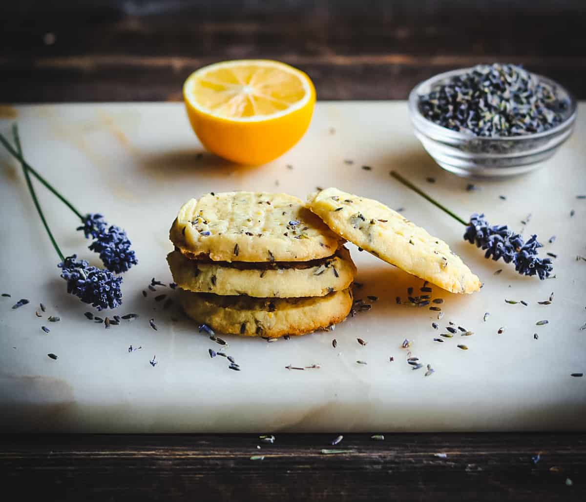 a stack of lemon lavender shortbread cookies on a board with lavender flowers