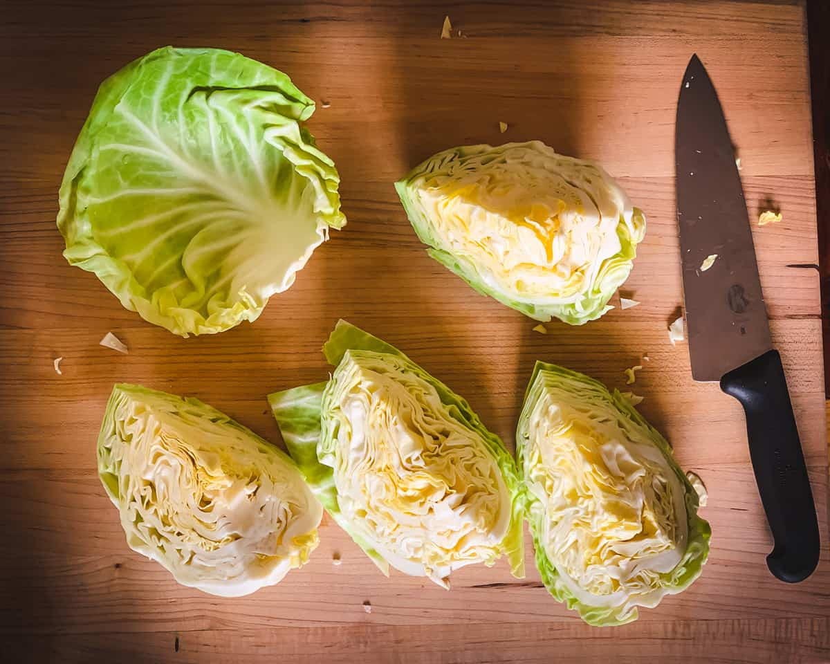 a cutting board with cabbage quarters and a cabbage leaf