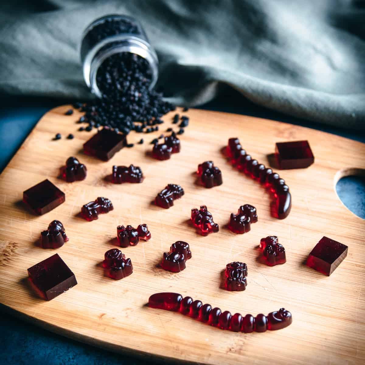 various elderberry gummies on a wooden board with dried elderberries