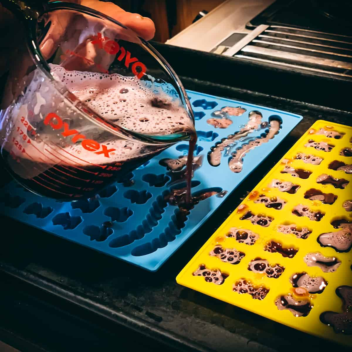 pouring the elderberry gummy mix into molds