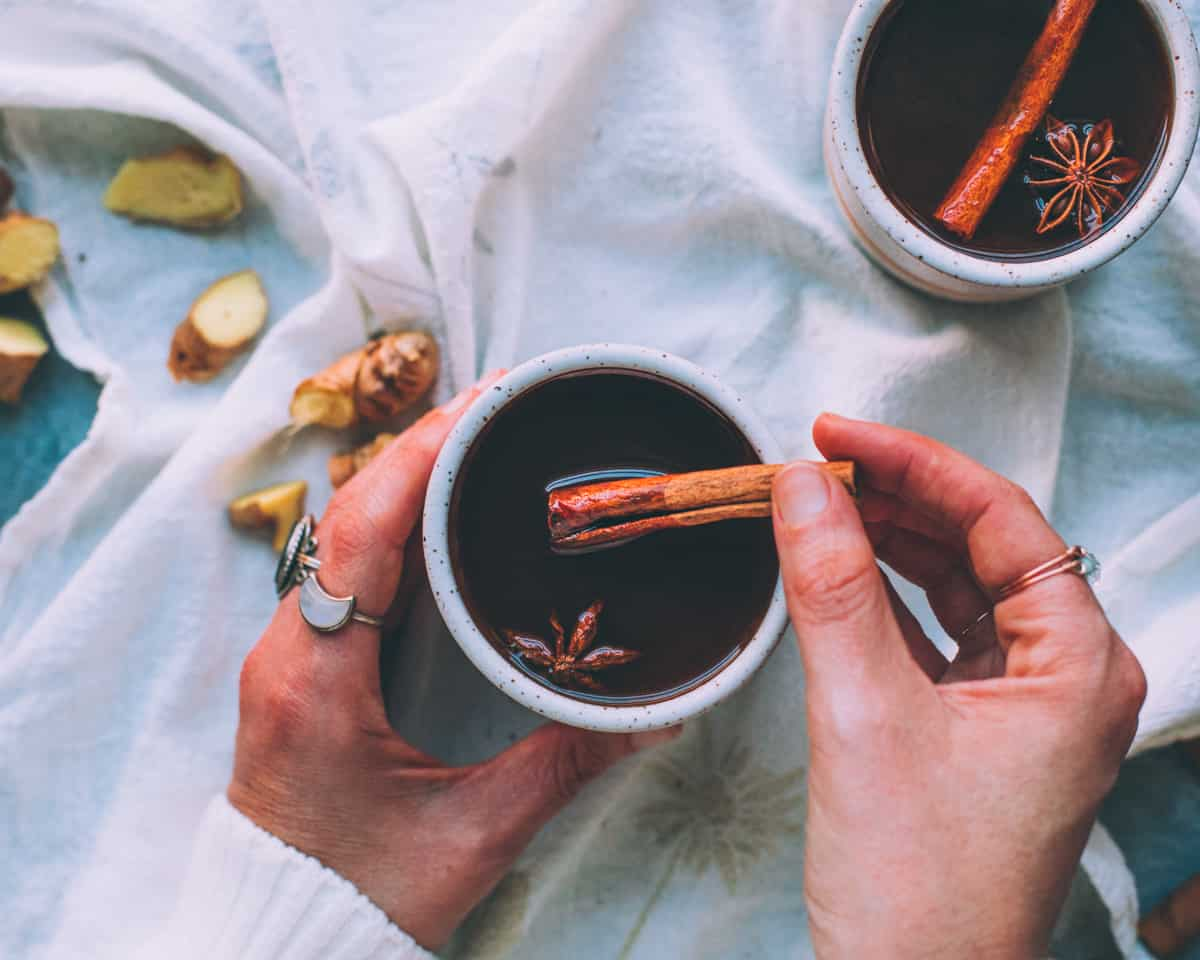 a woman's hands holding a mug of black chai with a cinnamon stick