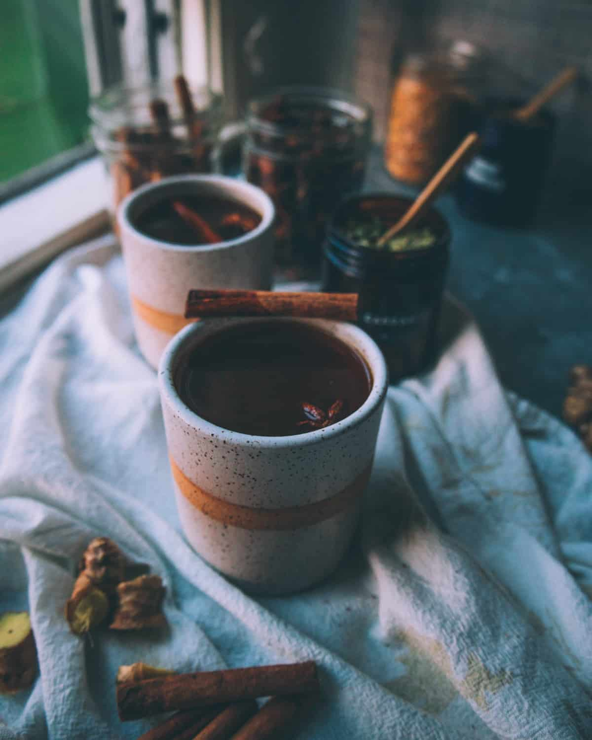 two mugs of black chai garnished with a cinnamon stick
