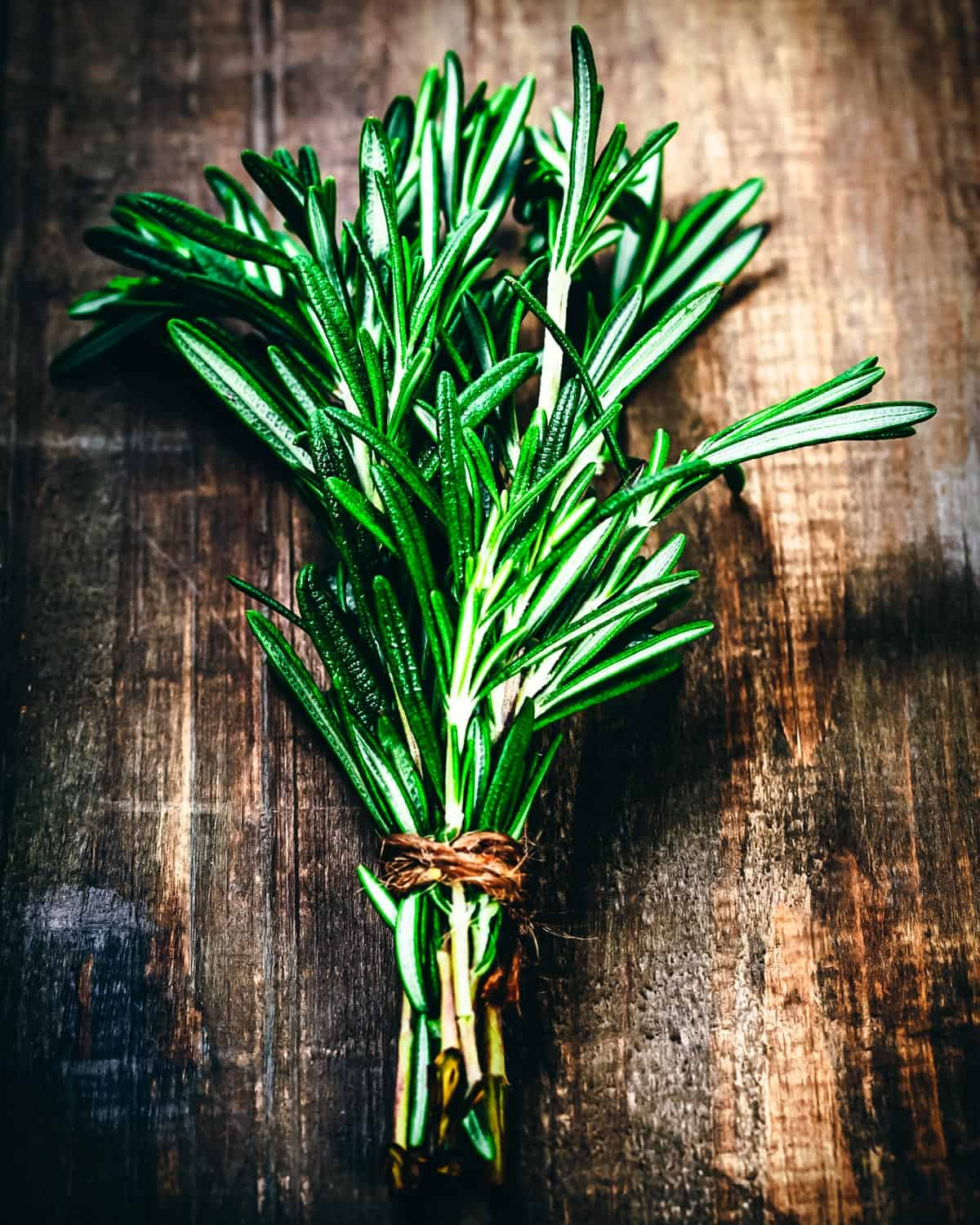 a bundle of rosemary on a wooden table