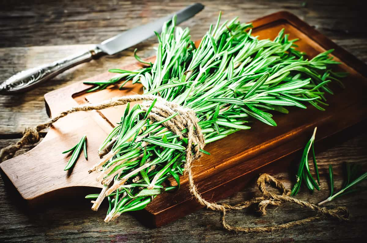 a bundle of rosemary on a cutting board