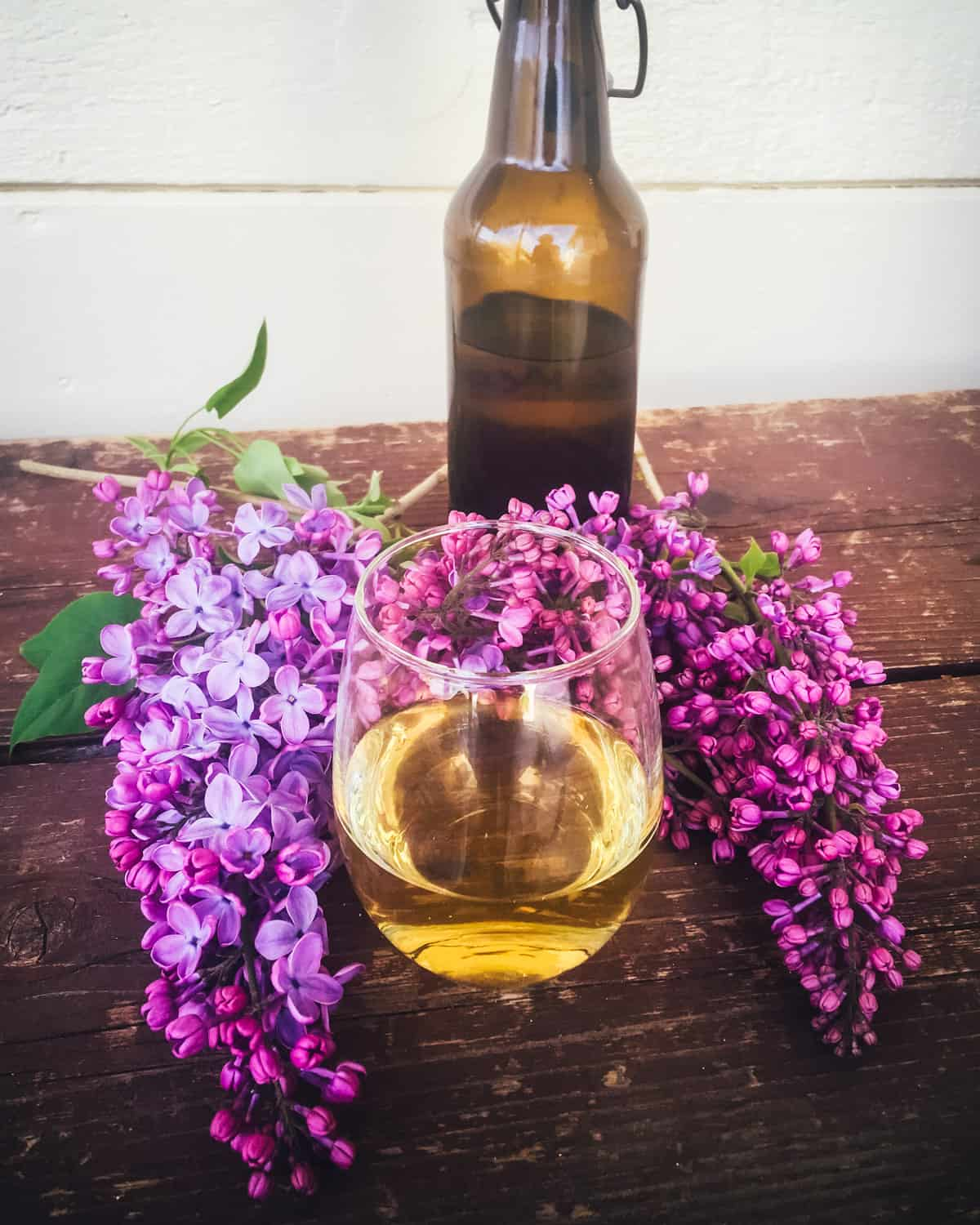 a bottle and glass of lilac mead on a table with lilac flowers