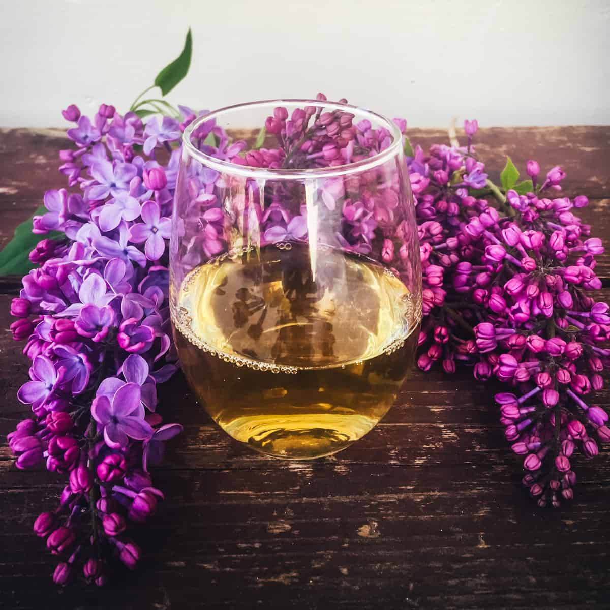 a glass of lilac mead on a table with lilac flowers