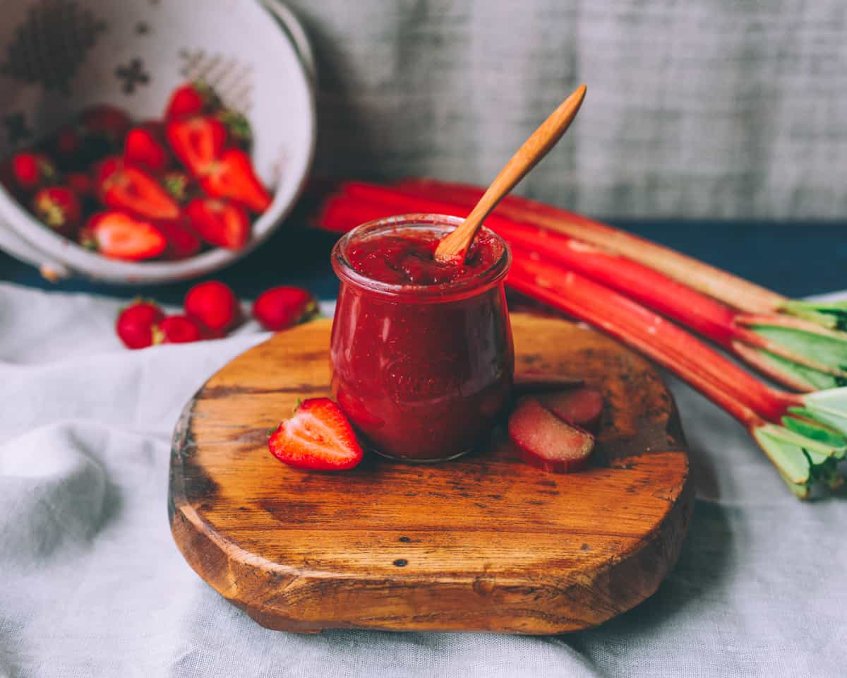 a jar of strawberry rhubarb butter on a wooden board