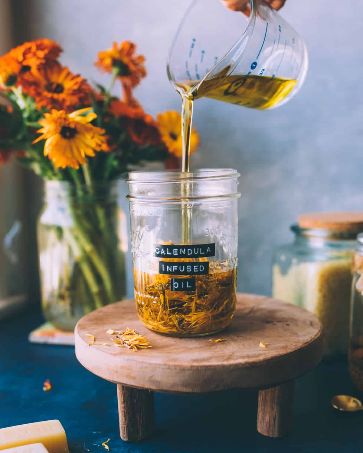 a hand pouring oil into a jar with dried calendula flowers