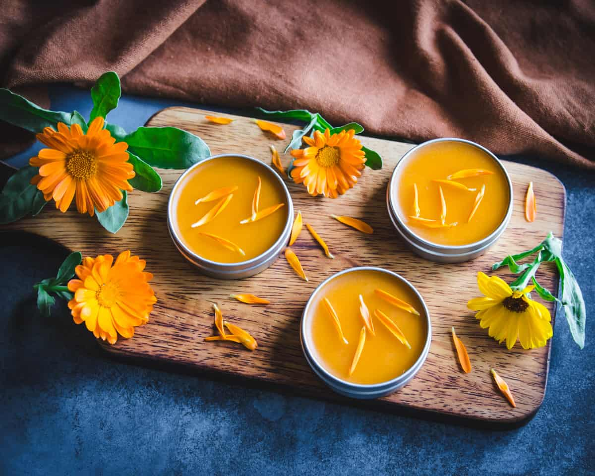 homemade calendula salve on a wooden cutting board with flowers